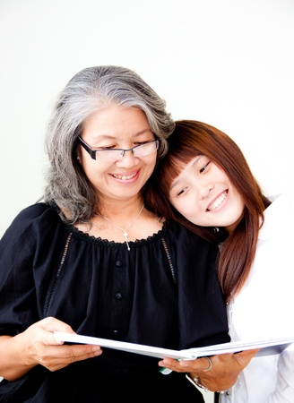 grandparent: senior asian woman enjoy reading with her granddaughter
