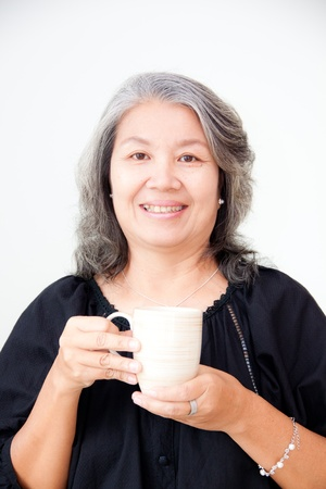 smiling senior asian woman holding a cup photo