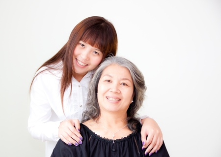 asian old woman: young asian woman standing beside her grandmother Stock Photo