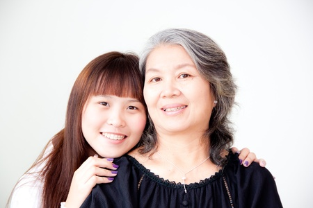 endearing: young asian woman hugs her grandmother