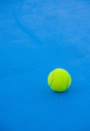 tennis ball on blue hard court