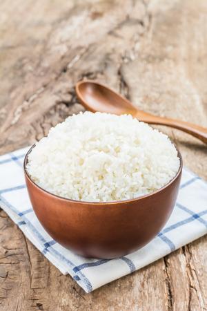 Le riz cuit dans un bol avec une cuillère et un torchon sur la vieille table en bois