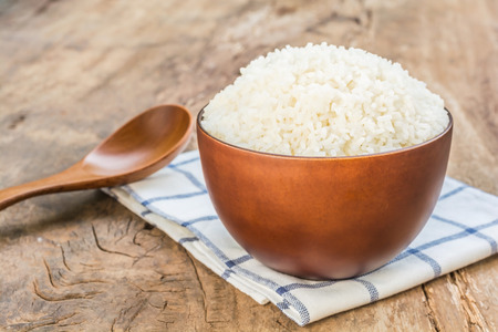 dishcloth: Cooked rice in bowl with spoon and dishcloth on old wooden table