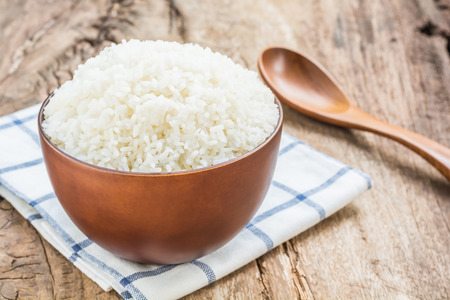 Cooked rice in bowl with spoon and dishcloth on old wooden table