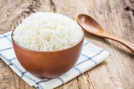 Gekookte rijst in kom met lepel en vaatdoek op oude houten tafel Stockfoto