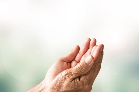 mano de dios: Dos abiertas las manos vacías de la mujer mayor con desenfoque de fondo