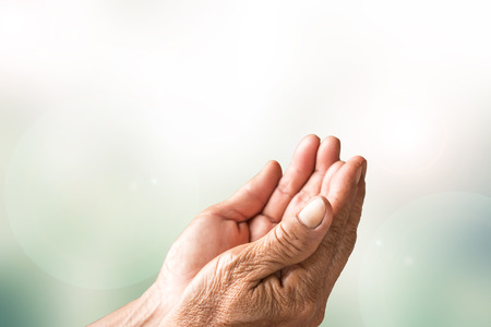 worship hands: Two open empty hands of old woman with blur background Stock Photo