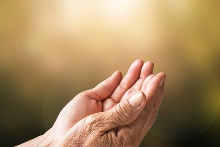 Twee open lege handen van de oude vrouw met een wazige achtergrond