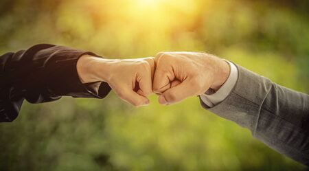 Fist bump collide agreement of two businesspeople, show strength teamwork, handshake negotiations finish together after good deal,panoramic banner.