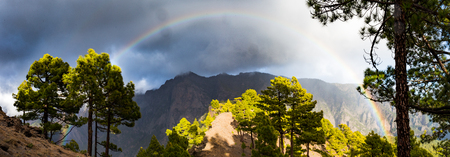 rainbow in front of mountains during stormy weather