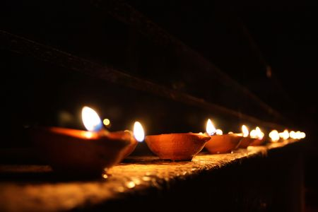 ethnic festival: A background with a beautiful line of traditional lamps lit on the occasion of Diwali festival in India.
