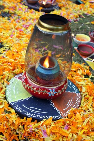 A traditional colorful lamp lit on the occasion of Diwali festival in India, in between decoration of flower petals. Stock Photo - 4722967