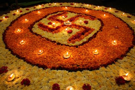 arranged: A background with a view of earthen lamps arranged on the holy Swastika design made of flowers, during Diwali festival in India.