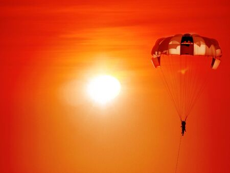 A beautiful background of a parasailing parachute on the backdrop a sunset on an evening sky. Stock Photo - 4722860