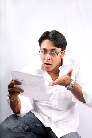 A young Indian businessman shocked looking at the billed amount.