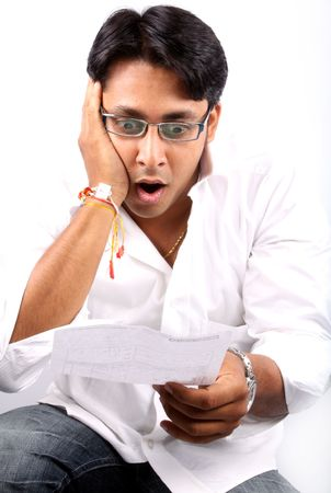 billed: A young Indian businessman shocked looking at the billed amount.