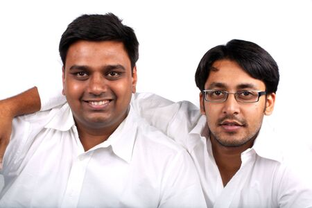 A friendship portrait of two young handsome Indian guys, on a white background