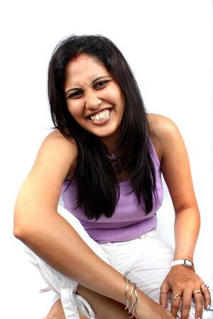 indian style sitting: A beautiful Indian lady with a laughing cutely, on white studio background. Stock Photo