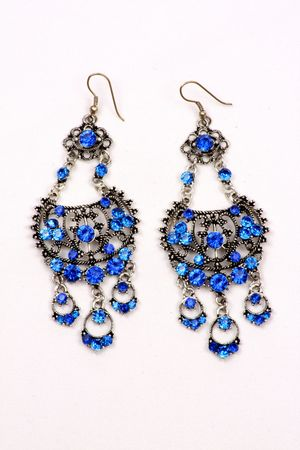 A set of beautiful ethnic earrings with blue gemstones in traditional Indian design, on a white fabric. Stock Photo