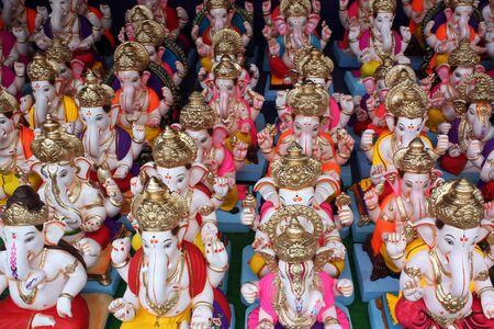 A religious background with an abstract view of the beautiful idols of the Hindu elephant god - Ganesha in blue and orange colors. Stock Photo - 5430696