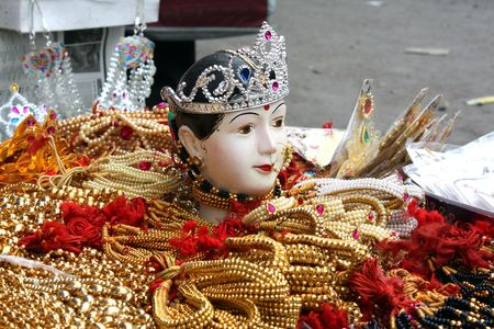 A goddess face kept in between precious jewelery for sale in a traditional Indian festival. Stock Photo - 5430713