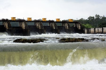 rains: Dam waters violently coming out of the flood gates of an Indian dam in the monsoon season. Stock Photo