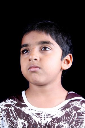 A portrait of sad pouting boy, on black studio background.