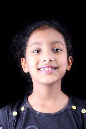 sincere girl: A portrait of a cute Indian smiling girl, on a black studio background.