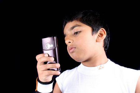 A young East Indian boy checking the calling number on his cellphone, on black studio background. photo