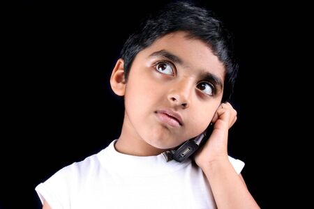 phonecall: A little Indian kid on a phonecall which is getting him worried, on black studio background.
