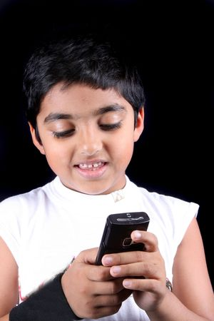 A young East Indian boy sending a text message on his cellphone, on black studio background. photo