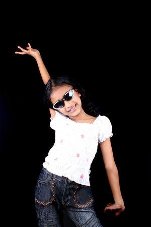 A cute Indian girl wearing sunglasses striking a dance pose, on black studio background.