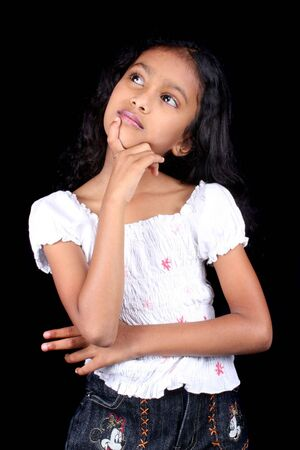 A potrait of a cute thinking Indian girl, on black studio background. Stock Photo
