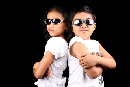 brother sister fight: A portrait of two stylish Indian kids posing back to back making faces, on a black background.