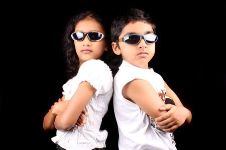 A portrait of two siblings posing as rivals, on black studio background.
