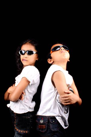 A portrait of two stylish Indian kids posing back to back making faces, on a black background. photo
