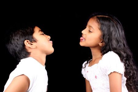 A portrait of an Indian brother and sister teasing each other, isolated on a black studio background.
