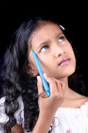A metaphorical image of a little Indian girl holding a blue pen thinking of an answer during her examination paper, on black studio background. Stock Photo