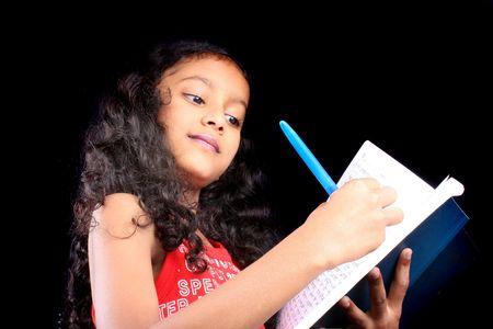 ni�o modelo: Un cansado indiecita tratando de escribir en el libro de la tarea pesada que est� completando.