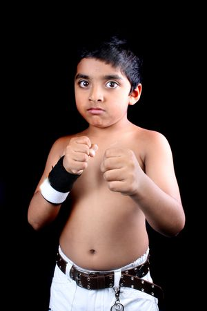 brat: A portrait of an angry Indian boy showing his fist telling that he is ready for fight, on black studio background.