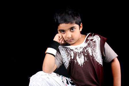 A portrait of an Indian boy standing in style, on black studio background. photo