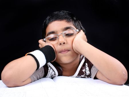 A metaphorical portrait of a little Indian boy tired doing his homework  studies. Stock Photo