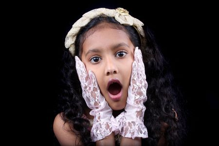 children acting: A portrait of a cute Indian girl with a shocked expression, on a black background. Stock Photo