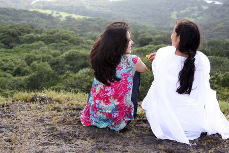 Two beautiful Indian ladies who are best friends having a happy time sharing gossips  during their vacation, on the hillside.