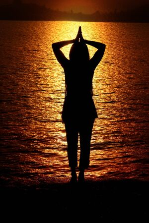A silhouette of a hindu woman traditionally praying to Sun God in the morning, on the banks of a river. Stock Photo - 5430719