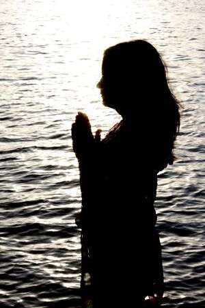 A beautiful background with a silhouette of an Indian woman praying by the river, borded by sparkling water. Stock Photo - 5430651