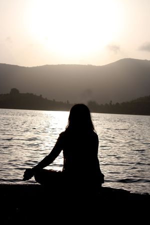 A spiritual Indian woman meditating on the riverbanks, in the morning. Stock Photo - 5430690