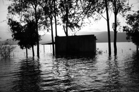 A vintage background with a view of a riverside home half-submerged in the flood waters during the Indian monsoons.