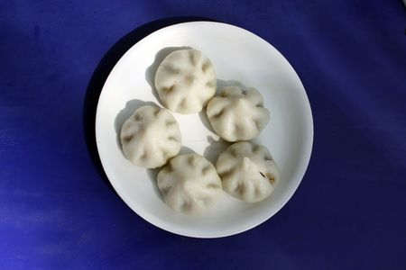 A background with a view of a plate containing traditional sweet called Modak which is only made during Ganesh festival in India.