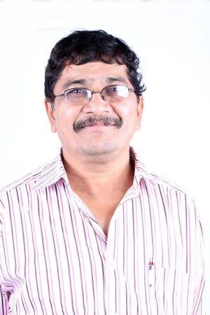 A portrait of a middle-aged Indian man, on a white studio background.